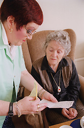 Carer and elderly woman reading list,
