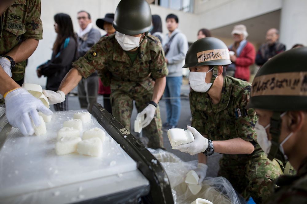 KUMAMOTO, JAPAN - APRIL 20: Self-Defense Forces personnel distribute food for evacuated earthquake survivors on early morning on April 20, 2016 in Mashiki Gymnasium evacuation center, Kumamoto, Japan. As of April 45 people were confirmed dead after strong earthquakes rocked Kyushu Island of Japan. Nearly 11,000 people are reportedly evacuated after the tremors Thursday night at magnitude 6.5 and early Saturday morning at 7.3.<br /> <br /> Photo: Richard Atrero de Guzman