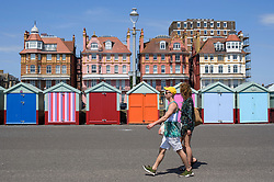 © Licensed to London News Pictures. 03/07/2018. Hove, UK. A young couple walk past colourful beach huts on the seafront at Hove, East Sussex on the south coast of England, as a heatwave continues across the UK. Photo credit: Ben Cawthra/LNP