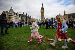 © Licensed to London News Pictures. 20/02/2017. London, UK. Two young Canadian gils play carry bunting of the Canadian flag during protest held by foreign nationals, living in the UK, outside the Houses of Parliament in London as members of the House of Lords debate the article 50 bill. Photo credit: Ben Cawthra/LNP