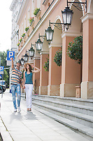 Tourist couple walking on sidewalk along building