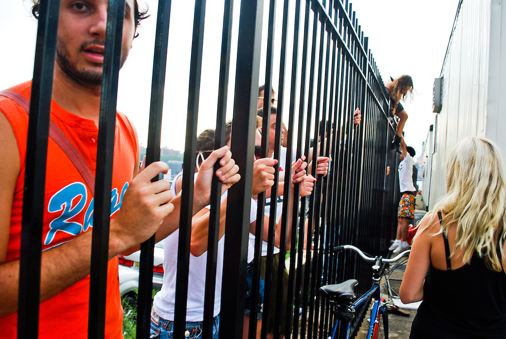 Denied at the gate due to park capacity limits, concert goers hop the fence behind the VIP trailer at the JELLY Pool Party free concert series East River State Park, Williamsburg, Brooklyn, New York