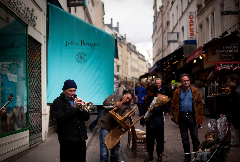 A street musician plays music on the Rue Mouffetard in the Latin Quarter in Paris.