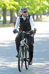 ©Licensed to London News Pictures 14/04/2020  <br /> Greenwich, UK. A police officer on patrol on his bike. Sunny weather in Greenwich park, Greenwich, London as people get out of the house from coronavirus lockdown to exercise. Photo credit:Grant Falvey/LNP