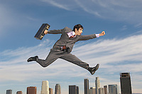 Business man running mid-air above city