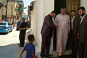 Hamas leader and deposed Palestinian prime Minister Ismail Haniya is greeted by bodyguards as he steps from his home in the Shatta camp to attend Friday prayers at a local mosque August 03, 2007 in Gaza. Haniya and Hamas have both been under extreme political pressure from outside Gaza since Hamas' violent takeover of the strip in June..