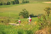 Two people cycling through Rio Setenil valley, Cuevas del Marques, Serrania de Ronda, Spain