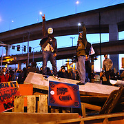 Occupy Seattle protesters stand atop a barricade on Monday, December 12, 2011 at the Port of Seattle. Hundreds of anti-Wall Street protesters gathered at the port and tried to shut down operations. Protesters scuffled with police during the rally and police used pepper spray and two flash-bang grenades to disperse the crowd after a protester threw a lit road flare toward officers. Another threw red paint on officers.