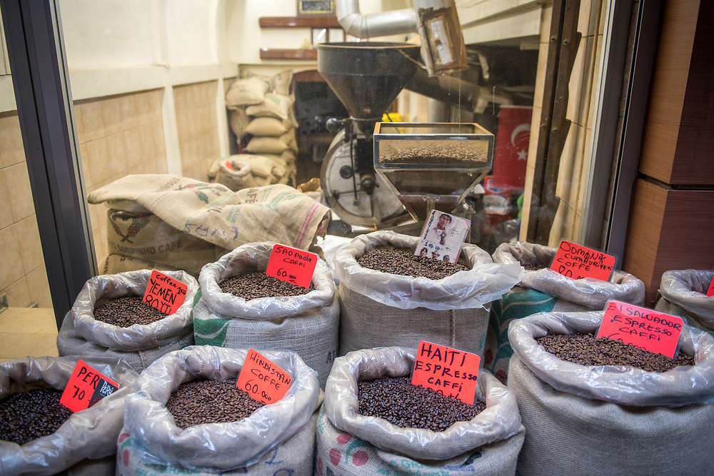 In front of a shop are linen bags filled to the brim with a variety of different blends of roasted coffee beans,  Istanbul, Turkey.