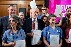 © Licensed to London News Pictures. 27/11/2019. London, UK. Labour Party Leader Jeremy Corbyn stands with NHS staff holding copies of an unredacted report on trade negotiations with the USA which allegedly includes the NHS. Photo credit: Rob Pinney/LNP