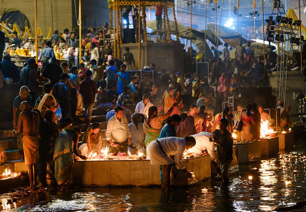 Varanasi, INDIA - CIRCA NOVEMBER 2018: People at night on the ghats of Varanasi during Dev Deepawali celebration. Varanasi is the spiritual capital of India, the holiest of the seven sacred cities and with that many rituals and offerings are performed daily by priests and hindus.
