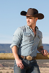 rugged cowboy leaning on a split rail wooden fence on a ranch