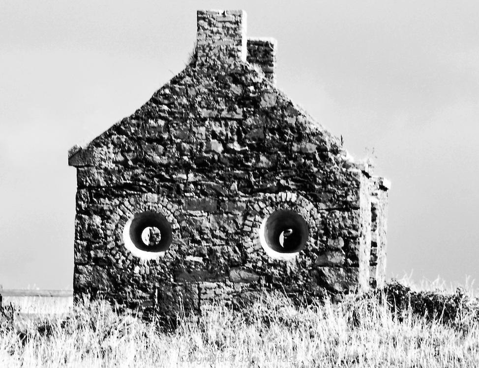 An abandoned house outside of Sligo, County Sligo, Ireland in black and white.  The configuration of the house and deep set windows gives the impression that it has a face.