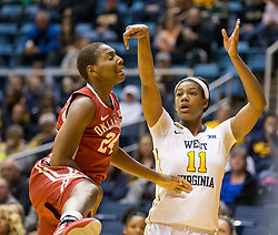 West Virginia Mountaineers forward Teana Muldrow (11) shoots a three pointer over Oklahoma Sooners guard Sharane Campbell (24) during the first half at the WVU Coliseum.