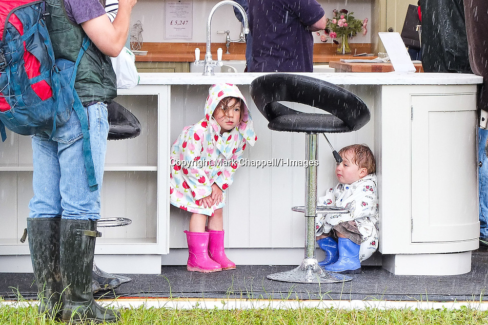 On the first day of summer, children shelter from the rain on a kitchen stand at The Cotswold Show held in Cirencester Park, Gloucs as it suffers a torrential downpour. Saturday 30  June  2012.  Cirencester, UK.<br /> Photo Credit: Mark Chappell<br /> <br /> &copy; Mark Chappell 2012. <br /> All rights reserved, see instructions.