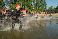 Competitors enter the water at Opechee Point for the swim portion of the GLCAC Marshmallow Man Sprint Triathlon on Sunday morning.  (Karen Bobotas/for the Laconia Daily Sun)
