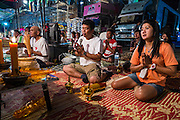 22 NOVEMBER 2013 - BANGKOK, THAILAND: Performers and members of the crew of the Prathom Bunteung Silp mor lam troupe pray before a performance in Bangkok. Mor Lam is a traditional Lao form of song in Laos and Isan (northeast Thailand). It is sometimes compared to American country music, song usually revolve around unrequited love, mor lam and the complexities of rural life. Mor Lam shows are an important part of festivals and fairs in rural Thailand. Mor lam has become very popular in Isan migrant communities in Bangkok. Once performed by bands and singers, live performances are now spectacles, involving several singers, a dance troupe and comedians. The dancers (or hang khreuang) in particular often wear fancy costumes, and singers go through several costume changes in the course of a performance. Prathom Bunteung Silp is one of the best known Mor Lam troupes in Thailand with more than 250 performers and a total crew of almost 300 people. The troupe has been performing for more 55 years. It forms every August and performs through June then breaks for the rainy season.     PHOTO BY JACK KURTZ