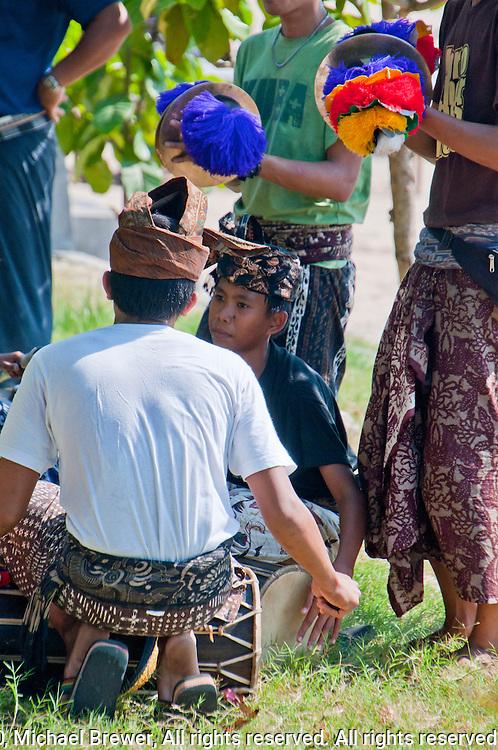 Boys playing gamelan music at a funeral in Jimbaran, Bali, Indonesia