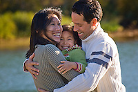 An asian mom and caucasian dad play with their daughter at Green Lake, Whistler.