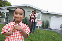 Portrait of boy (5-6) in front of new house, parents in background