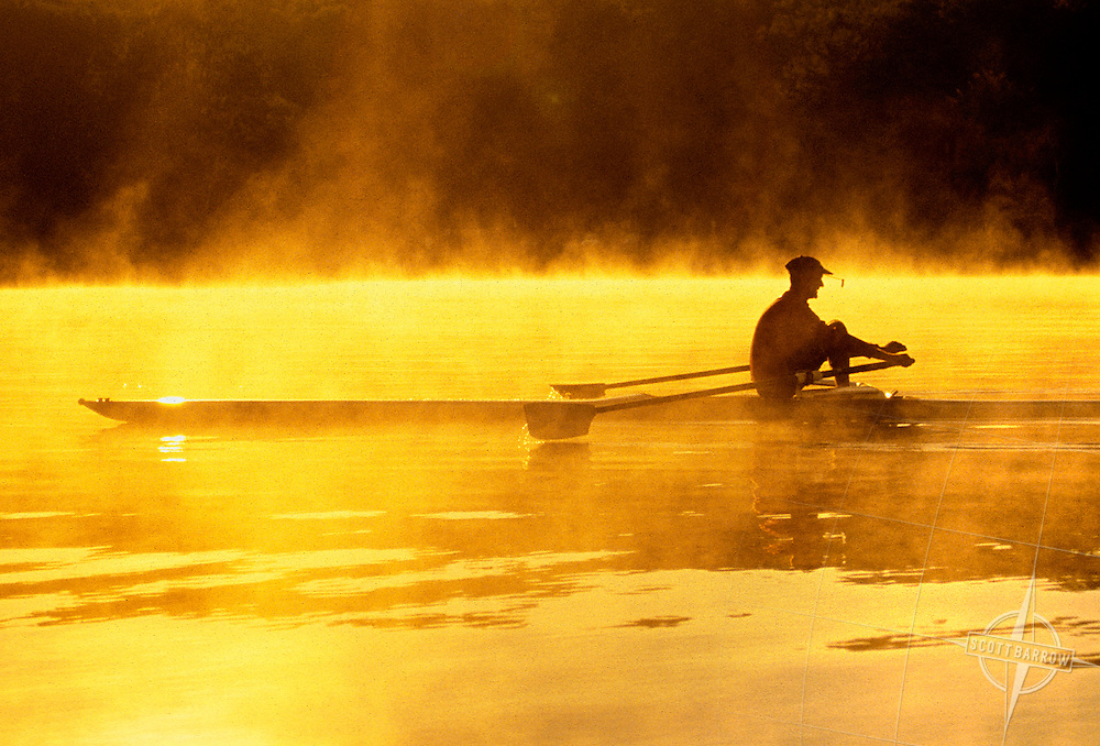 Senior Man rowing a scull on lake.