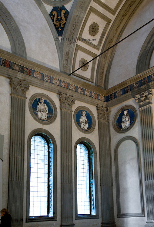 Interior of the Pazzi Chapel showing one corner with arched windows and terra cotta roundels by Luca della Robbia above them.   The grey edgings and  pilasters are of pietra serena, a specific type of stone from Fiesole.  Combined with the warm white walls they make an exquisitely serene space.  Some scholars now think that Berunelleschi was responsible for the design, and the building work was completed by others, such as Michelozzo.