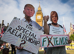 London, June 21st 2017. Protesters march through London from Sheherd's Bush Green in what the organisers call 'A Day Of Rage' in the wake of the Grenfell Tower fire disaster. The march is organised by the Movement for Justice By Any Means Necessary and coincides with the Queen's Speech at Parliament, the destination. PICTURED: A couple in masks protest against the relationship between Trump and May.