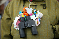 Closeup detail of binoculars and racing badges around th eneck of a racegoer during Champion Day of the 2018 Cheltenham Festival at Cheltenham Racecourse.