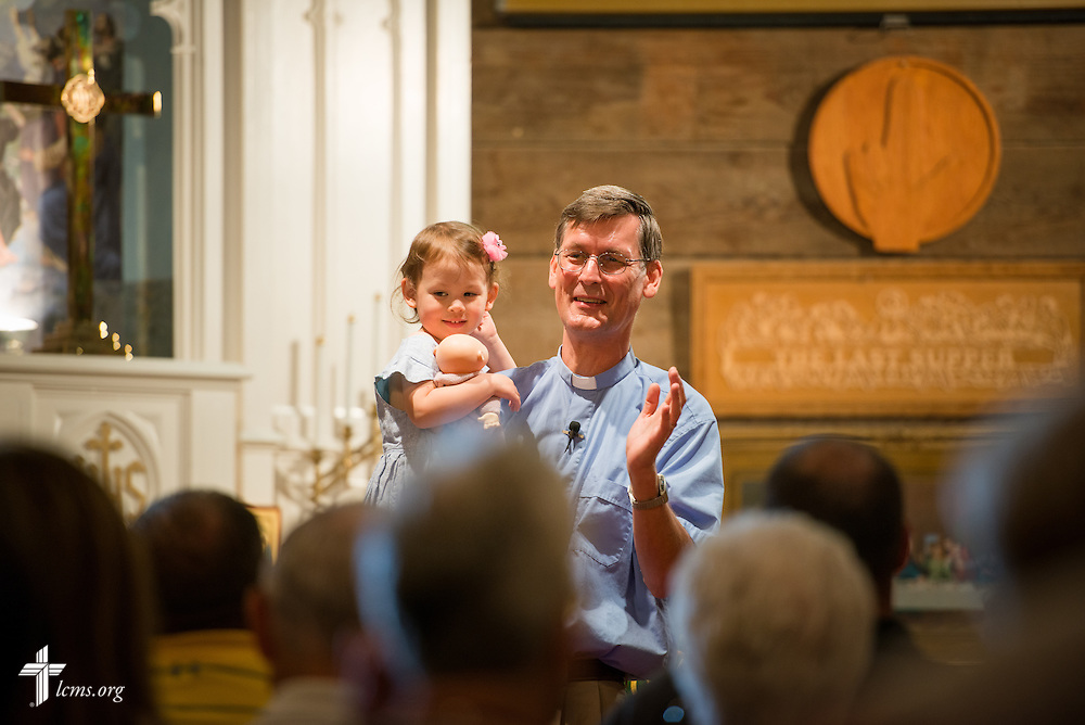 The Rev. Stephen Oliver, career missionary in the Asia Pacific region at China Lutheran Seminary in Hsinchu, Taiwan, holds his daughter Virginia as he preaches during worship in the sanctuary and mission museum during at Mission Central on Sunday, July 19, 2015, in Mapleton, Iowa. LCMS Communications/Erik M. Lunsford