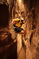 A young man navigates a slot canyon while canyoneering in southern Utah.
