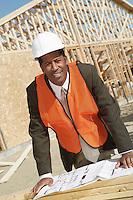 Surveyor Reading Blueprints on Construction Site