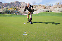 Full length of senior male golfer celebrating a putt at golf course
