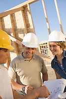 Two men and woman with blueprints at construction site, portrait