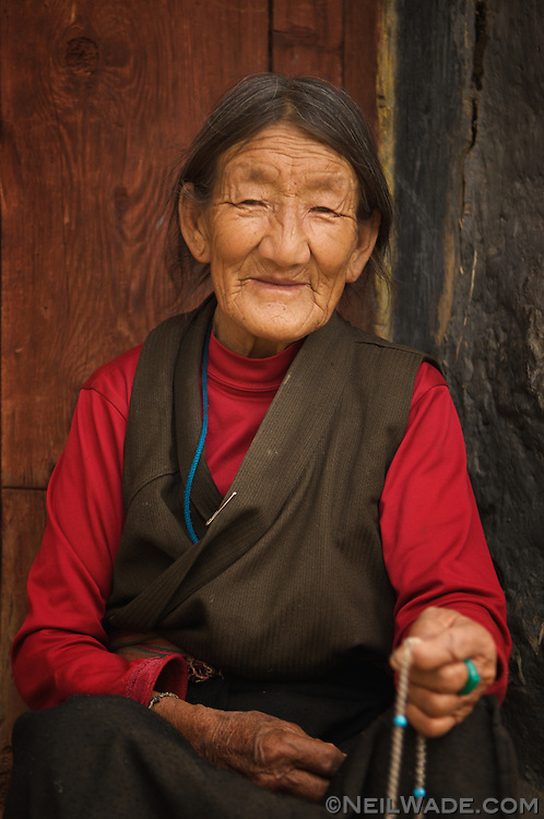 An elderly Tibetan woman sits on her doorstep and counts prayer beads in Ganzi, Tibet.