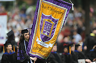 Katie Doyle carries the banner for the University of Mississippi's School of Law during graduation ceremonies in the Grove, in Oxford, Miss. on Saturday, May 11, 2013.
