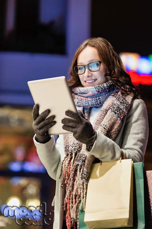 Portrait of young attractive woman smiling and using digital tablet while on night shopping