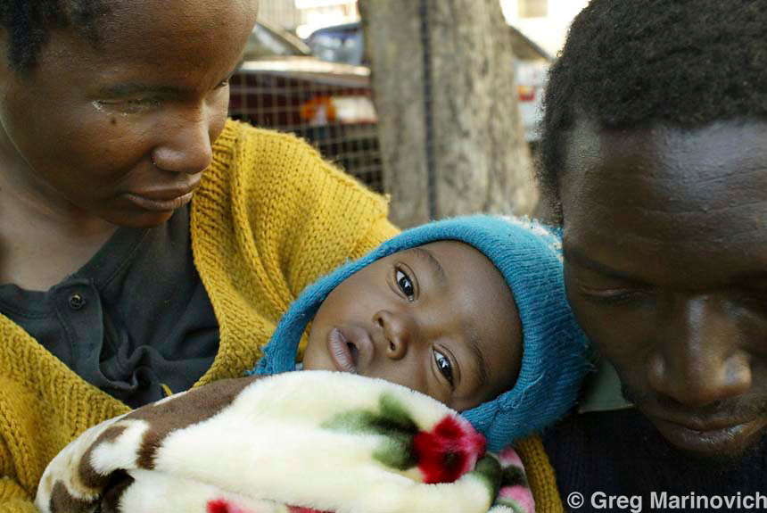 SOUTH AFRICA JOHANNESBURG July 14, 2005. A blind Zimbabwean couple, Peter and Mes Ndlovu, crouch on a sidewalk with their sighted child, Brian Ndlovu (4 months) after they and several hundred people were evicted from a Bree Street office block being illegally used as apartments in downtown Johannesburg July 14, 2005. Dozens of blind Zimbabweans make a living by begging on Johannesburg's streets. Greg Marinovich