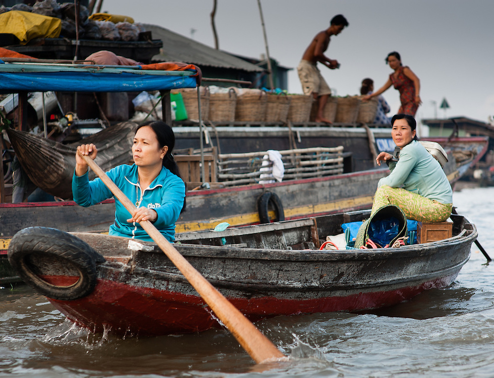 Two women paddling on a boat on the Mekong delta (Vietnam)