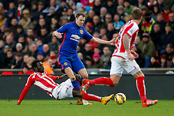 Jonny Evans of Manchester United is challenged by Mame Biram Diouf of Stoke City - Photo mandatory by-line: Rogan Thomson/JMP - 07966 386802 - 01/01/2015 - SPORT - FOOTBALL - Stoke-on-Trent, England - Britannia Stadium - Stoke City v Manchester United - New Year's Day Football - Barclays Premier League.