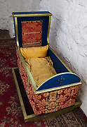 Old rocking cradle for a baby. Comlongon Castle is a restored Medieval Scottish tower house dating from the late 1400s. Guests can stay in the attached Edwardian hotel, a baronial style mansion built 1900-02, set in 120 acres of manicured gardens, sweeping lawns, carp pond, lakes and woodlands, near Clarencefield and Dumfries, in southwest Scotland, United Kingdom, Europe. Originally built by the Murrays of Cockpool, Comlongon Castle remained in the Murray family until 1984. The castle is 50 feet square and stands 70 feet high, with walls over 4 meters thick, with impressive displays of weapons, armor and banners.
