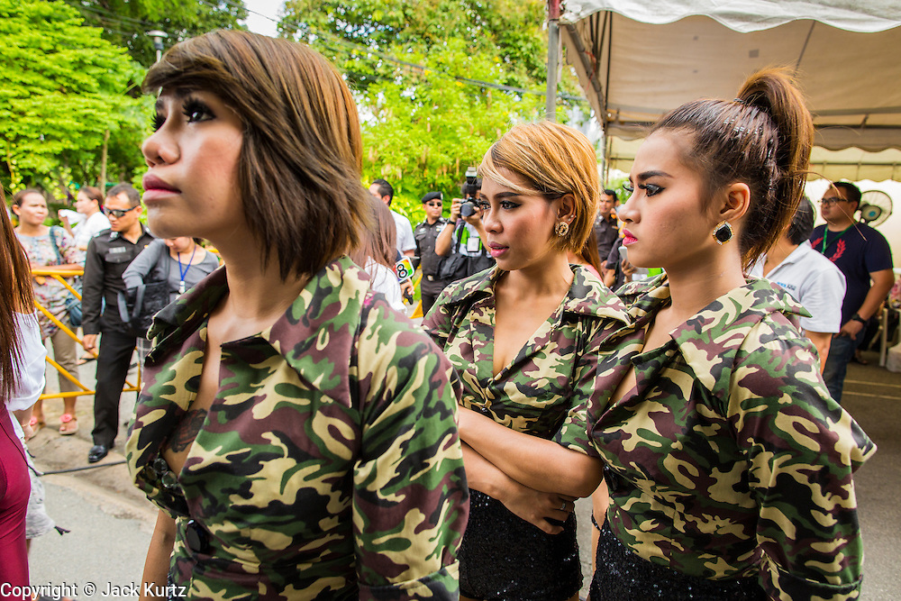 "15 JUNE 2014 - BANGKOK, THAILAND: ""Coyote dancers"" wait to perform in military style camouflage shirts during a ""Return Happiness to Thais"" party  in Lumpini Park in Bangkok. The Thai military junta, formally called the National Council for Peace and Order (NCPO), is sponsoring a series of events throughout Thailand to restore ""Happiness to Thais."" The events feature live music, dancing girls, military and police choirs, health screenings and free food.   PHOTO BY JACK KURTZ"