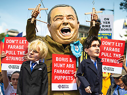 © Licensed to London News Pictures. 20/07/2019. London, UK. An anti-Brexit protester dressed as Nigel Farage carries puppets of Conservative Leadership candidates Boris Johnson and Jeremy Hunt at the start of the March for Change. Photo credit: Rob Pinney/LNP