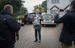 © Licensed to London News Pictures. 23/06/2016. Biggin Hill, UK. UKIP party leader Nigel Farage is seen at home holding a copy of The Sun newspaper before voting in the EU referendum. Polls have opened for voting - with counting starting after polls close at 10PM.Photo credit: Peter Macdiarmid/LNP