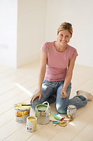 Woman kneeling on floor with painting materials