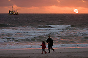 Sunset at the beach. Ship pumping up sand from off-shore to stabilize the beach, threatened by erosion caused by the North Sea waves.