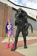 Garden City, New York, U.S. - June 14, 2014 - A young girl in a Twilight Sparkle costume from My Little Pony is with her father in an Alien costume, based on Alien VS Predator movie, in front of an historic Mitchel Field hangar at Eternal Con, the annual Pop Culture Expo, with costumes, Comic Books, Collectibles, Gaming, Sci-Fi, Cosplay, Horror, and held at the Cradle of Aviation Museum on Long Island.