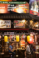 Two mean eating at an outside table beneath neon signs in the Kabukicho district, a popular centre of nightlife and entertainment in Tokyo, Honshu, Japan