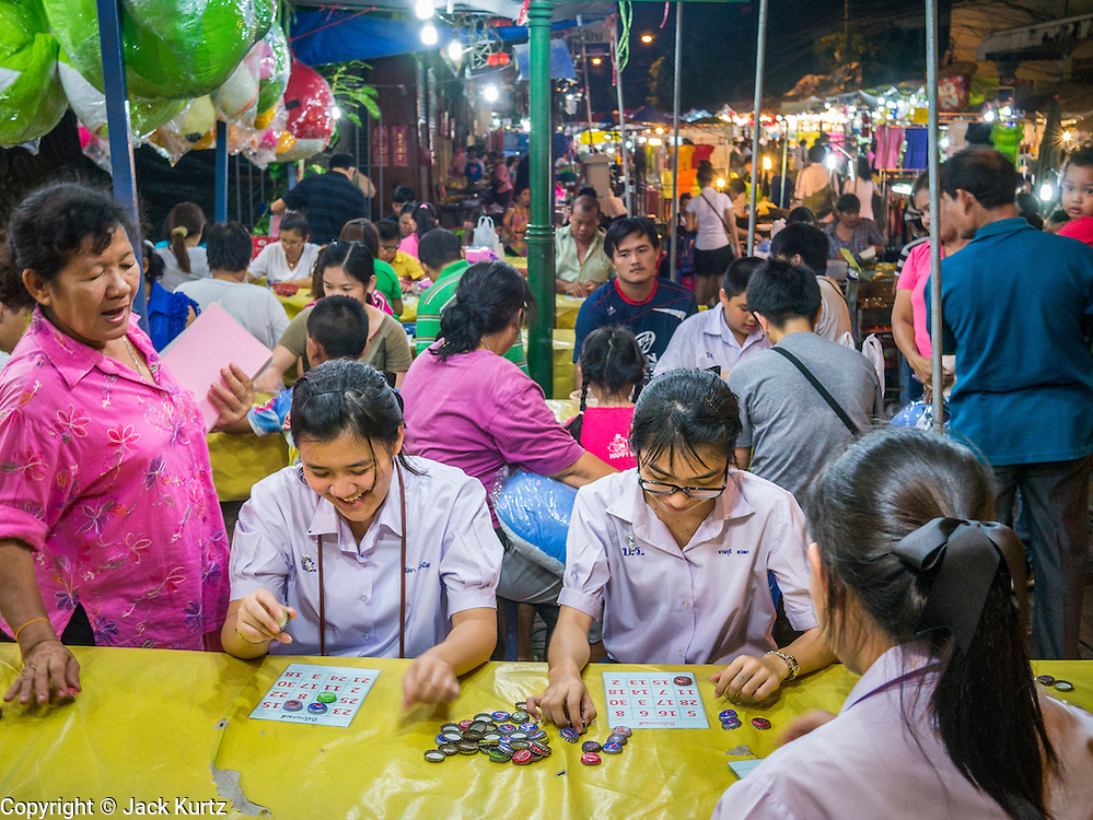 "27 NOVEMBER 2012 - BANGKOK, THAILAND:  School girls play bingo in the Bingo tent at the Wat Saket Temple Fair in Bangkok. Bingo is called Bingo in Thailand. Wat Saket, popularly known as the Golden Mount or ""Phu Khao Thong,"" is one of the most popular and oldest Buddhist temples in Bangkok. It dates to the Ayutthaya period (roughly 1350-1767 AD) and was renovated extensively when the Siamese fled Ayutthaya and established their new capitol in Bangkok. The temple holds an annual fair in November, the week of the full moon. It's one of the most popular temple fairs in Bangkok. The fair draws people from across Bangkok and spills out in the streets around the temple.   PHOTO BY JACK KURTZ"