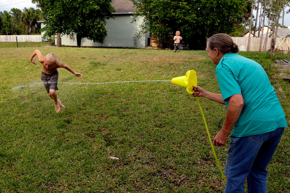 Giving into the temptation, Katherine Smith picks up the great grandchildren's new water toy and turns it on Jordan Thompson, 8. Laughter immediately fills the front lawn as Jordan darts back and forth, trying to avoid the spray. Greg Kahn/Staff