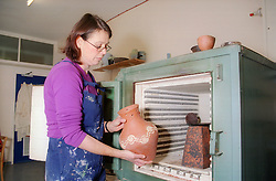Female potter placing pot into kiln,